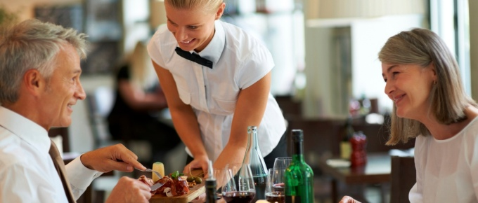 Smiling waitress serving dinner to senior couple at restaurant